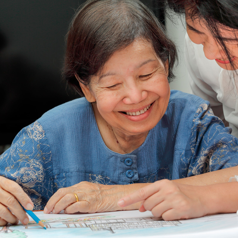 A senior and caregiver engaged in art therapy